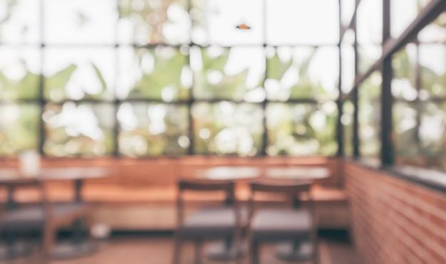 Interne abstrakte unschärfe des café-kaffeehauses, die mit hellem hintergrund des bokehs defokussiert ist