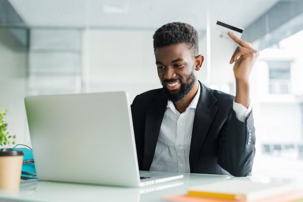 Internet-banking-verkäufe. erfolgreicher afrikanischer geschäftsmann, der an einem laptop sitzt und kreditkarte in der hand hält, bis geschäftsmann bestellungen über das internet tut