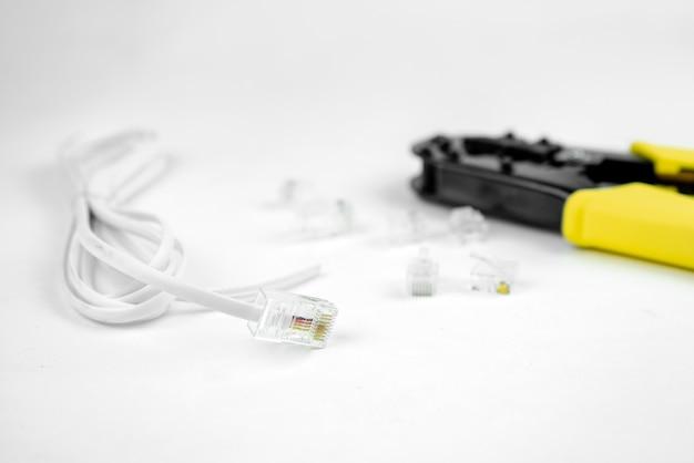 Internet- oder telefonleitungskabel mit crimper auf weißem hintergrund