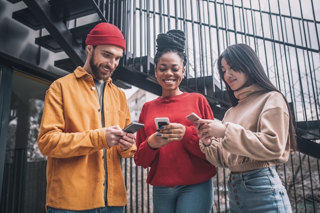 Internetabhängigkeit. drei freunde verbringen zeit miteinander online und sehen aufgeregt aus