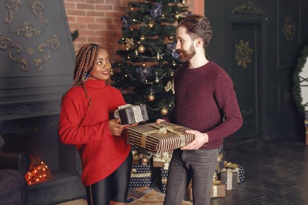 Internetionale menschen zu hause. paar in einer weihnachtsdekoration. afrikanische frau und kaukasischer mann.
