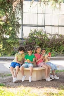 Internetsucht. grundschulkinder, die sich für smartphones interessieren, die an einem warmen wettertag im park sitzen