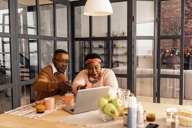Internetverbindung. nettes ehepaar, das mit den händen gestikuliert, während es einen videoanruf tätigt