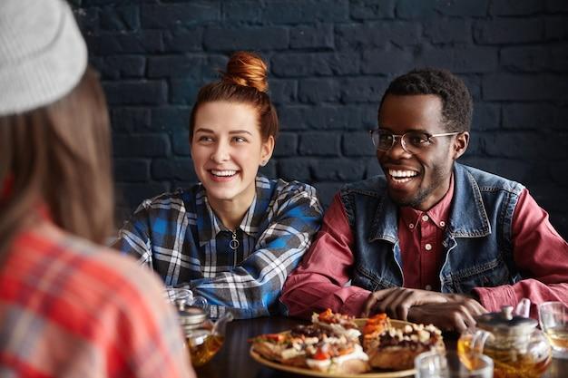 Interracial gruppe von drei freunden im restaurant speisen, gute zeit zusammen verbringen