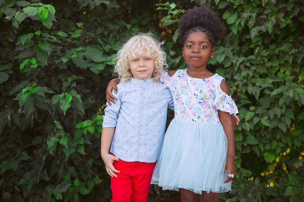 Interracial kinderfreunde mädchen und junge, die am sommertag zusammen im park spielen