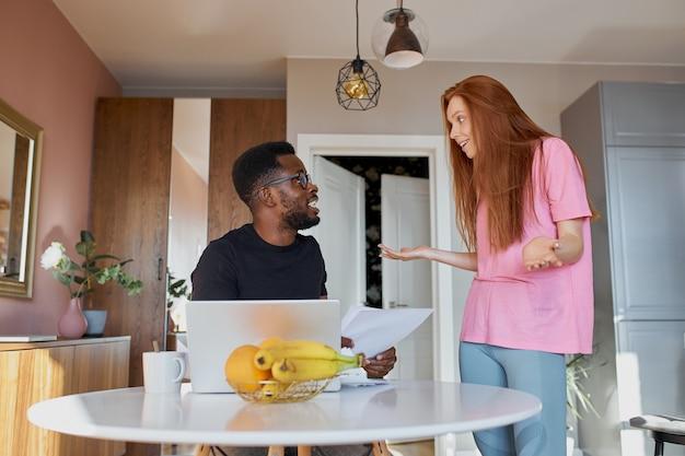 Interracial paar, das post liest und buchhaltung in der küche zu hause überprüft