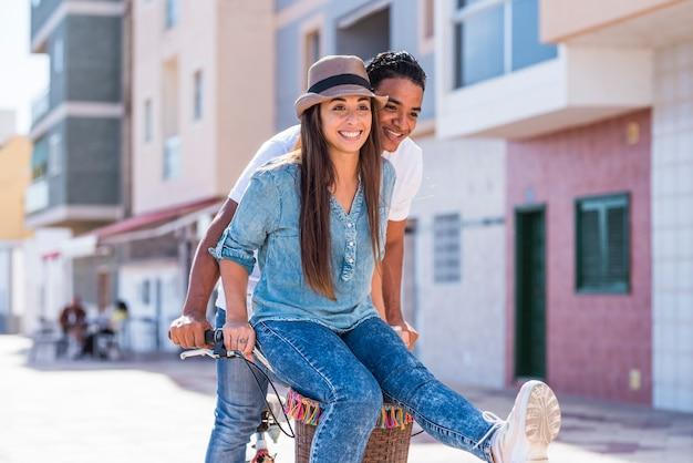Interracial paar haben spaß zusammen fahrrad fahren im freien in der stadt - glück und freude junge menschen interracial freund und freundin - zwei genießen aktiven lebensstil und liebe oder freundschaft