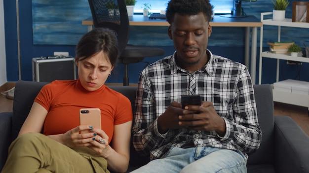 Interracial paar mit smartphones im wohnzimmer
