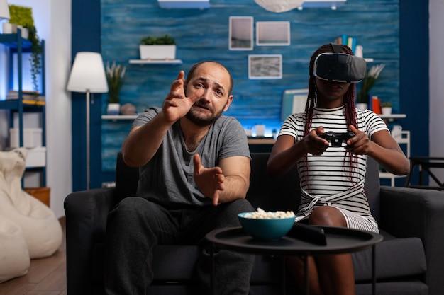 Interracial paar spielt mit vr-brille und controller