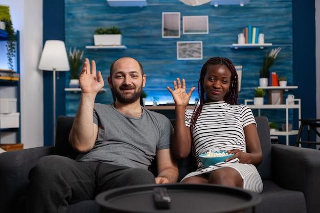 Interracial paar winkt videoanruf-kamera mit technologie