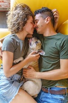 Intimer moment eines paares, das sich zu hause mit hund küsst. vertikale draufsicht, die mit haustier auf der couch spielt.