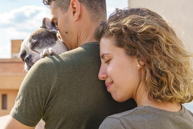 Intimer moment junger paare, die draußen hund küssen. horizontale seitenansicht eines paares, das seinen hund liebt.