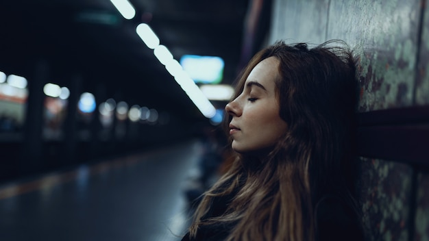 Intimes porträt der jungen frau, die innerhalb der u-bahnstation entspannt. reales bild des lebensstils.