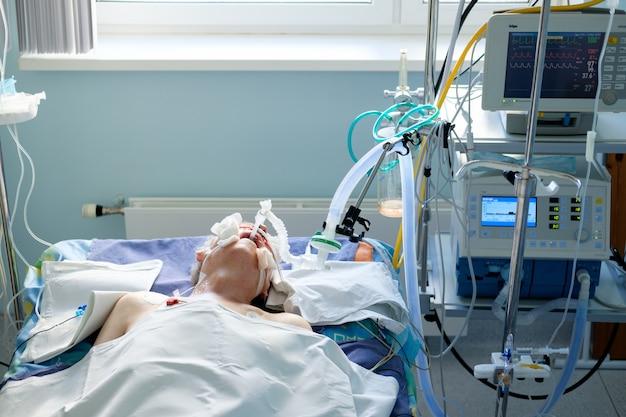 Intubierter erwachsener weißer mann unter avl im koma auf der intensivstation. patient in kritischem zustand.