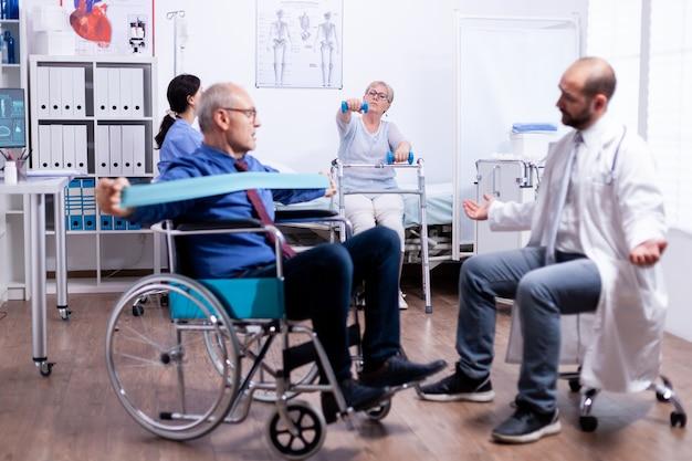 Invalide im rollstuhl, die muskelkraft zurückgewinnt, die im rehabilitationszentrum mit arzt arbeitet