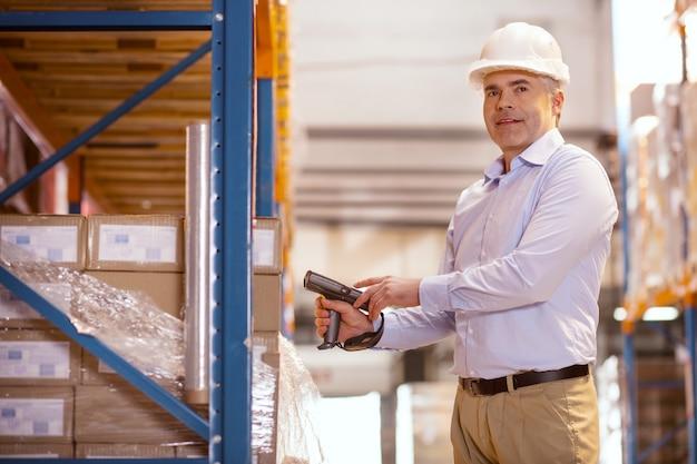 Inventarprüfung. freudiger netter mann, der die kisten scannt, während er sie für die lieferung vorbereitet
