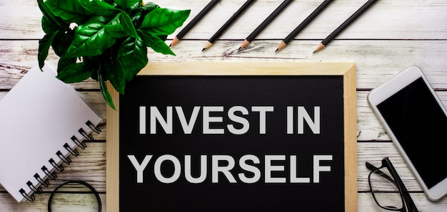 Invest in yourself steht in weiß auf einer tafel neben einem telefon, einem notizblock, einer brille, bleistiften und einer grünen pflanze