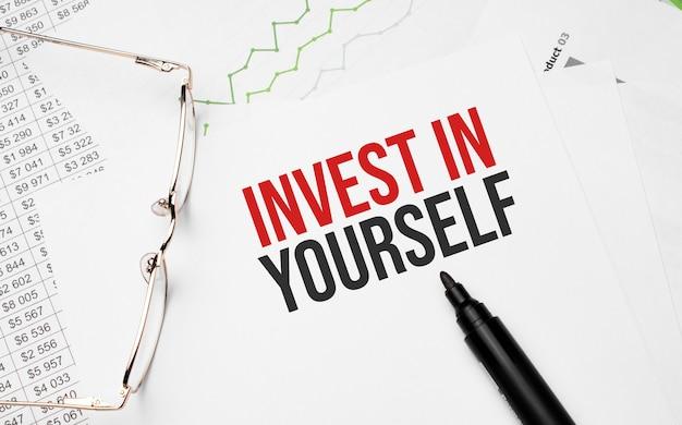 Investiere in dich selbst . konzeptioneller hintergrund mit diagramm, papieren, stift und brille