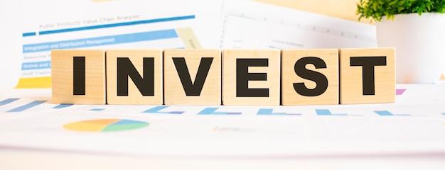 Investieren sie das wort in holzwürfel. hintergrund ist ein geschäftsdiagramm. geschäfts- und finanzkonzept