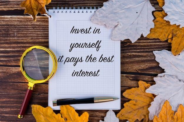 Investieren sie in sich selbst, es bringt das beste interesse, der text ist in ein weißes notizbuch geschrieben, mit herbstahorn, blättern und alten brettern.