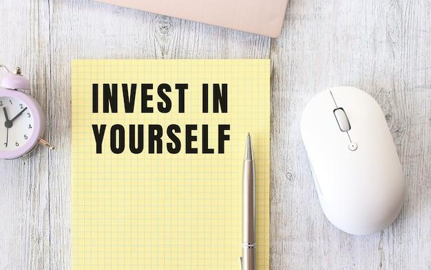 Investieren sie in sich selbst text geschrieben in einem notizbuch, das auf einem hölzernen arbeitstisch neben einem laptop liegt