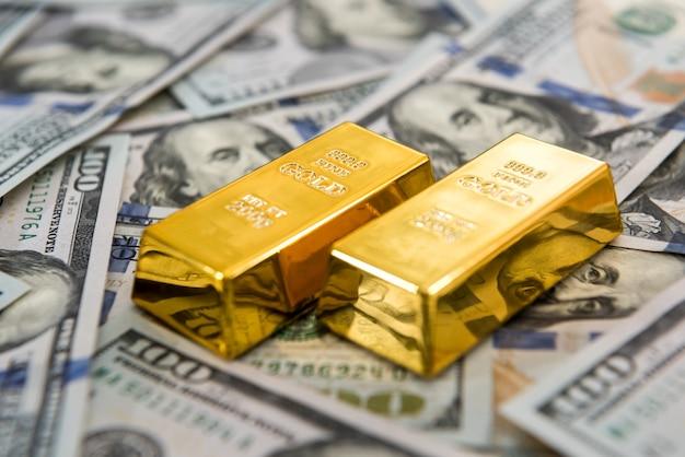 Investition in echtes goldbarren auf dollarnoten. geld und sparen konzept