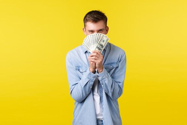 Investitions-, einkaufs- und finanzkonzept. fröhlicher, fröhlicher junger mann, der geld gegen das gesicht hält, mit entzückten lächelnden augen späht, sich lustvoll fühlt, bargeld in der lotterie gewinnt, gelber hintergrund.