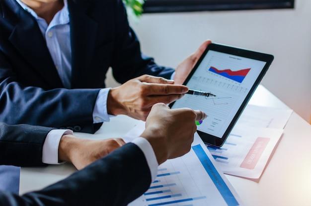 Investor des geschäftsmannes mit zwei partnern, der über finanzstatistik-diagramminformationen spricht