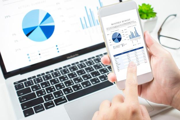 Investoren analysieren die investitionen in den markt mit einem finanzdashboard für telefone