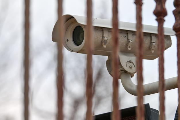 Ip-cctv-überwachungskamera und eisenzaun auf grauem himmelshintergrund, stadtbild