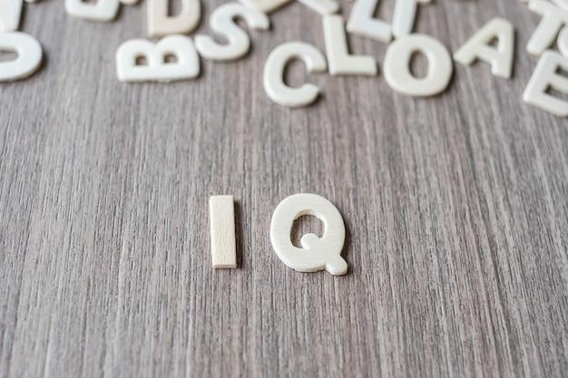 Iq-wort von buchstaben des hölzernen alphabetes. geschäfts- und ideenkonzept