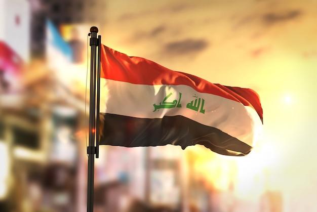 Irak-flagge gegen stadt verschwommen hintergrund bei sonnenaufgang hintergrundbeleuchtung