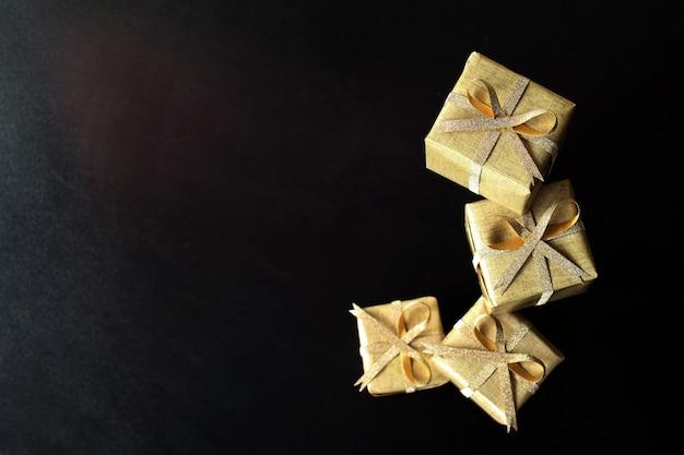 Irgendein goldenes geschenk verpackt auf schwarzem hintergrund, fokus auf spitzenkasten.