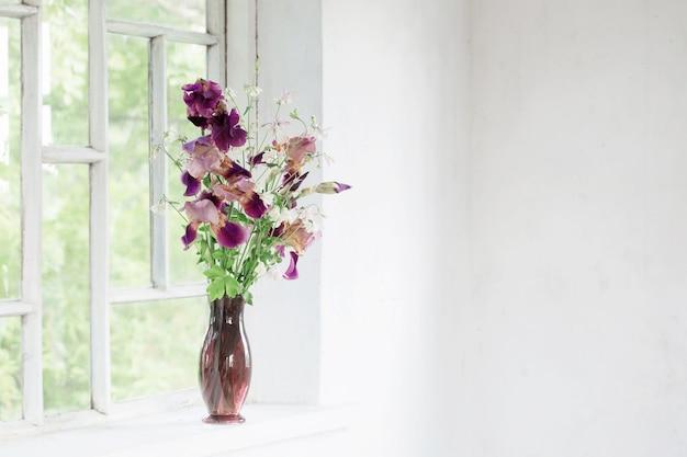 Irisblumen in glasvase auf weißer alter fensterbank
