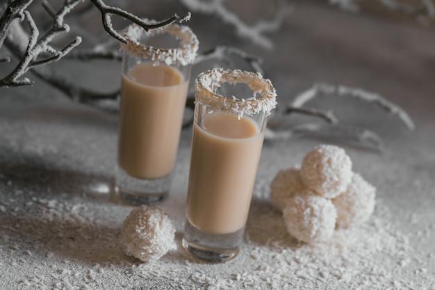 Irische sahne oder kaffeelikör mit hausgemachten gesunden kokosnussbällchen und kokosflocken auf hellem hintergrund