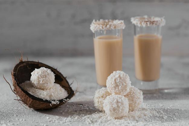 Irische sahne oder kaffeelikör mit hausgemachten gesunden kokosnussbällchen und kokosflocken auf heller oberfläche