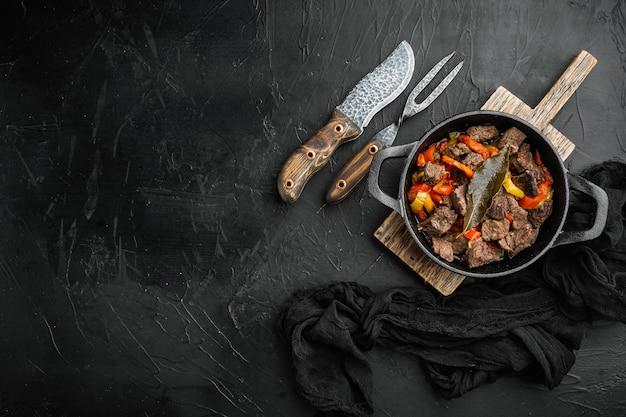 Irischer eintopf mit rindfleisch, kartoffeln, karotten und kräutern in einer gusseisernen pfanne auf schwarzem stein