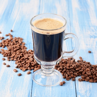 Irischer kaffee auf einem blauen hölzernen hintergrund mit kaffeebohnen