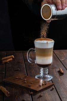 Irischer kaffee im transparenten glas auf holztisch. baristas hand streut zimt auf weißen schaum. kaffeestimmungskonzept mit kopienraum