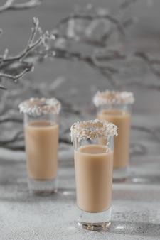 Irischer sahnelikör oder kaffeelikör mit kokosflockenkrone auf kurzem glas. winterfeiertagsdekorationen