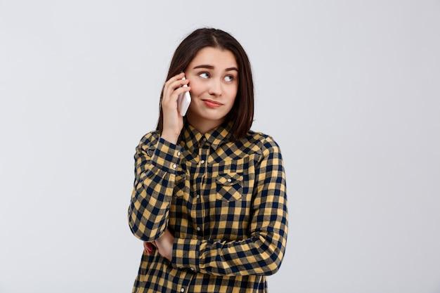 Ironisches junges schönes mädchen gekleidet im karierten hemd, das am telefon spricht und seite über weißer wand betrachtet.