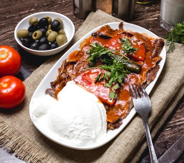 Iskender-kebab, garniert mit tomaten und petersilie, serviert mit joghurt