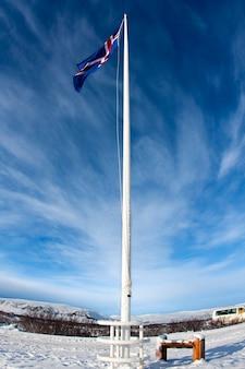 Isländische flagge unter blauem himmel
