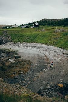 Isländische strandlandschaft, mann geht im pullover