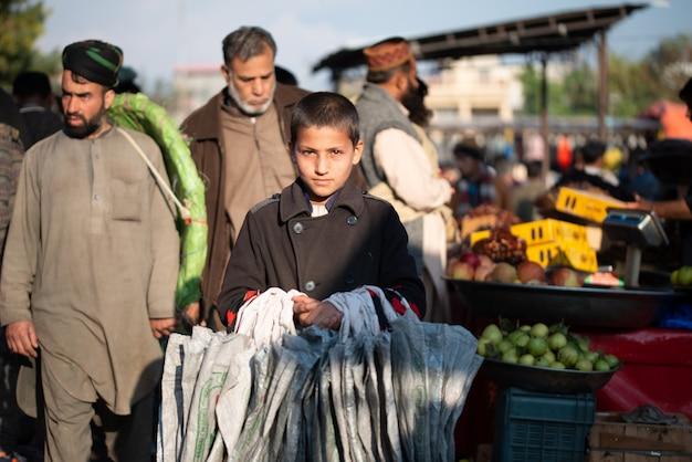 Islamabad, islamabad capital territory, pakistan - 2. februar 2020, ein junge verkauft tragetaschen auf dem gemüsemarkt.