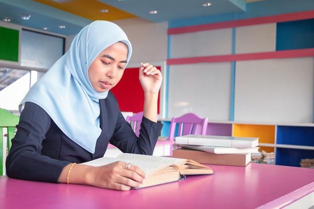 Islamische frau des jungen studenten. sie sitzt und liest ein buch.