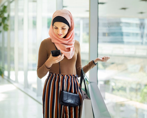 Islamische frau, die am telefon schaut