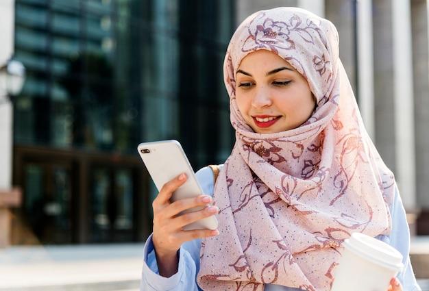 Islamische frau, die handy verwendet und kaffeetasse hält