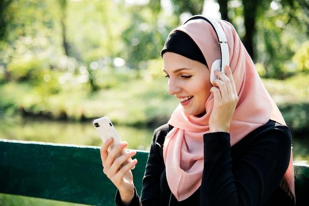 Islamische frau, die handy zur hörenden musik verwendet