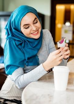 Islamische Frau, die intelligentes Telefon und das Lächeln verwendet